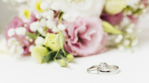 two-silver-wedding-rings-near-flower-bouquet_23-2148187502
